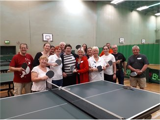 Group of people stood round a tablet tennis table all holding bats