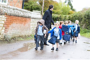children walking in double file with a teacher looking out for them all