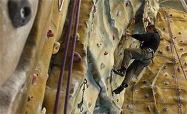 Man in a harness climbing the wall at Blackpool Sports Centre climbing wall