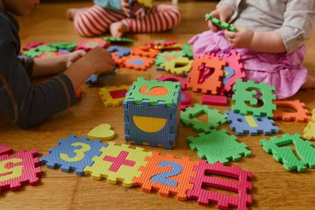 Little children on floor playing with large numbered jigsaw pieces.