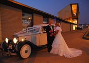 Bride and Groom stood by vintage car
