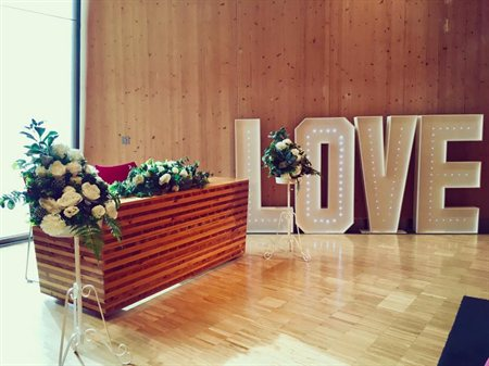 Table with flower displays and large illuminating LOVE sign