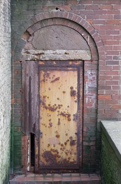 Badly rusting doors to disused toilets under promenade lift entrance