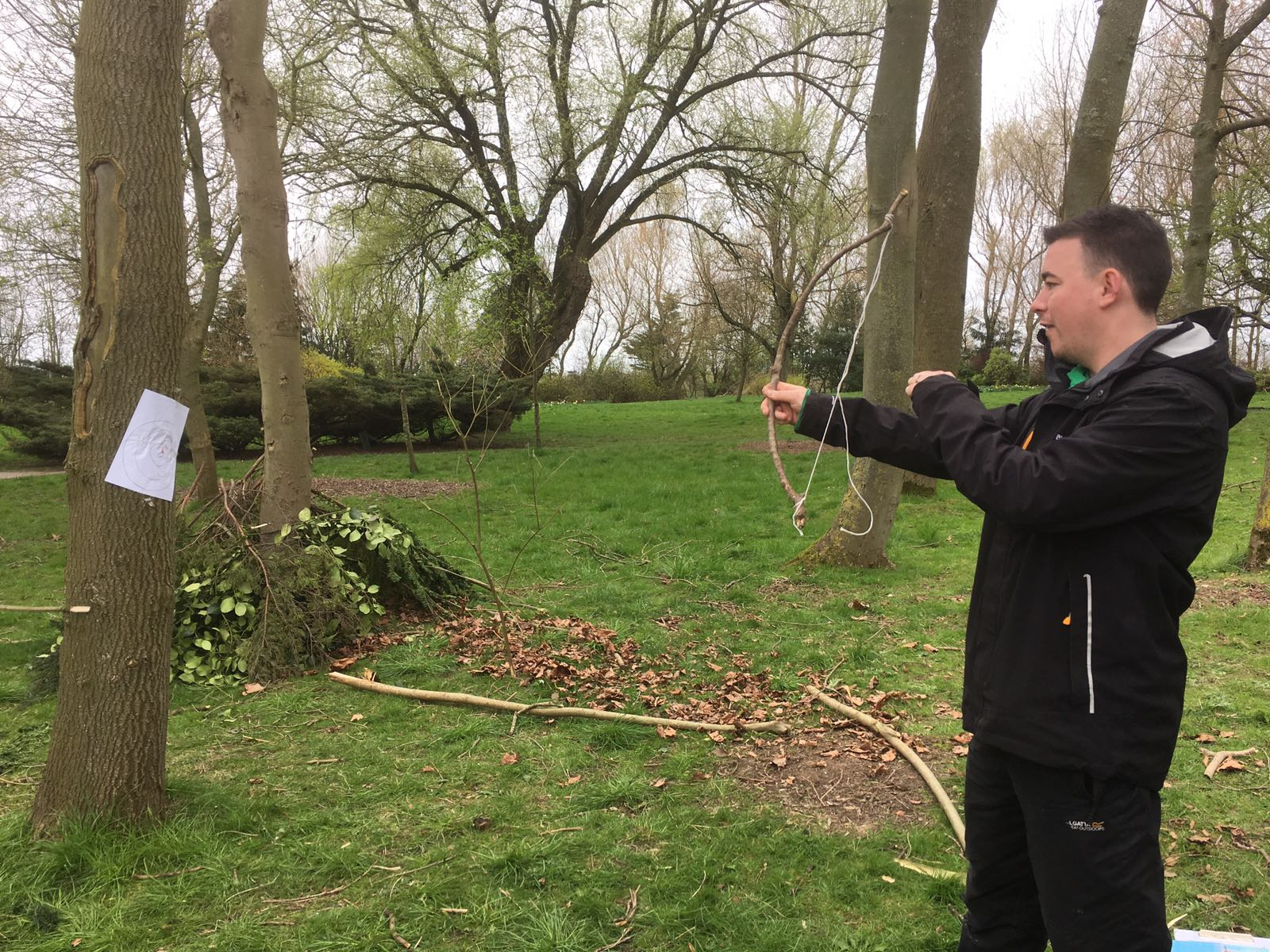 Man shooting a bow made of sticks and a string