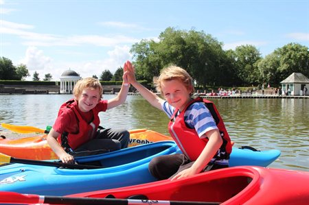 Two boys doing a high five whilst both sat in kayaks