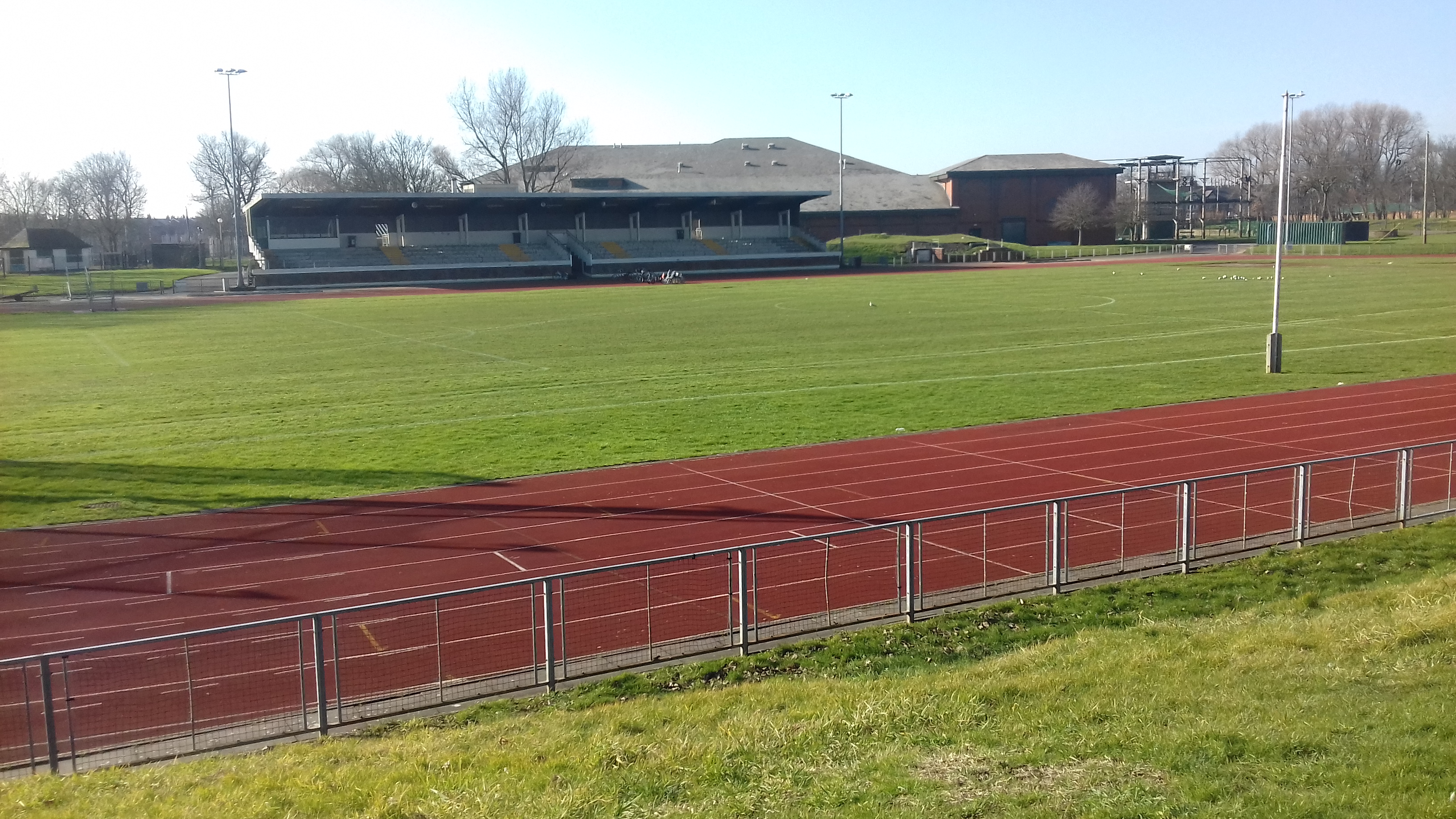 Outdoor athletics track and spectators stand.
