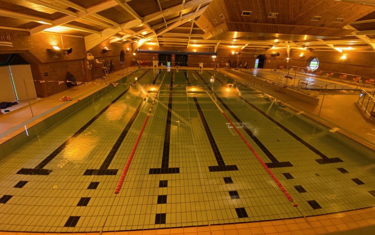 Inside Moor Parks pool hall, brick building with yellow lighting, main pool split into 3 sections for public swimming