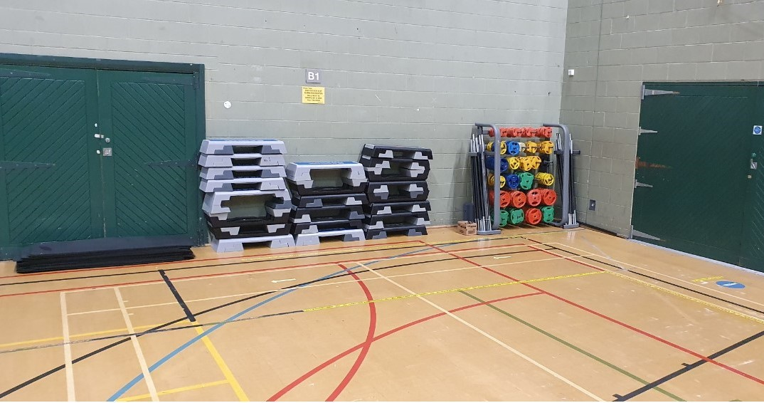 Exercise class equipment including mats, bodypump weights and step boxes stacked up to one side of the sports hall with socially distanced markings on the floor