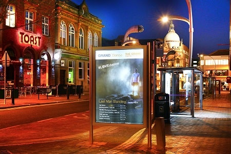 Illuminated advertising poster in town centre at night