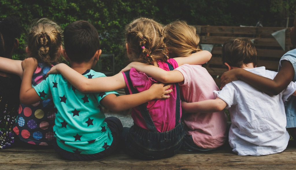 group-of-kindergarten-kids-friends-arm-around-sitting-together-picture-id671260342