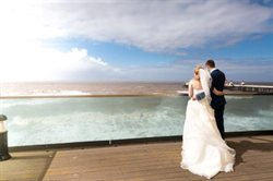 Bride and groom on balcony looking to sea.